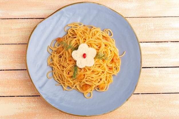 Вид сверху приготовленной итальянской пасты, вкусной еды с зеленью внутри синей тарелки на кремовой деревянной деревенской поверхности