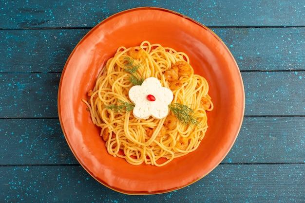 Вид сверху приготовленной итальянской пасты, вкусной еды с зеленью внутри оранжевой тарелки на синей деревянной деревенской поверхности