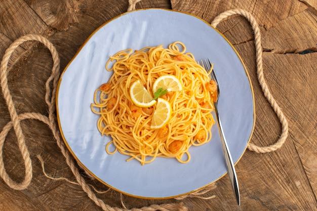 Вид сверху приготовленной итальянской пасты с зеленью и ломтиками лимона внутри синей тарелки с веревками на деревянной поверхности