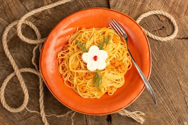 Вид сверху приготовленной итальянской пасты с зеленью внутри оранжевой тарелки на деревянном столе