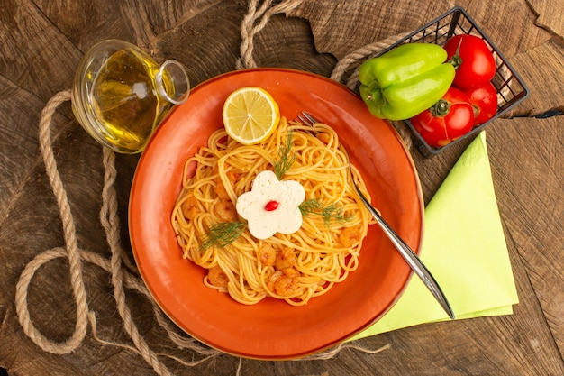 緑の海老とレモンスライス野菜とオレンジプレート内の油と一緒に調理されたイタリアンパスタのトップビュー