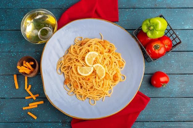 Вид сверху приготовленной итальянской пасты с ломтиками лимона внутри синей тарелки с маслом и овощами