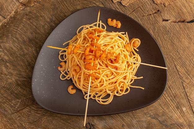 木製の表面に茶色のプレート内のエビと調理されたイタリアのパスタのトップビュー