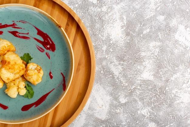 흰색 표면에 접시 안에 요리 슬라이스 콜리 플라워의 상위 뷰