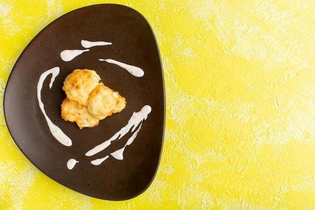 노란색 표면에 접시 안에 요리 슬라이스 콜리 플라워의 상위 뷰