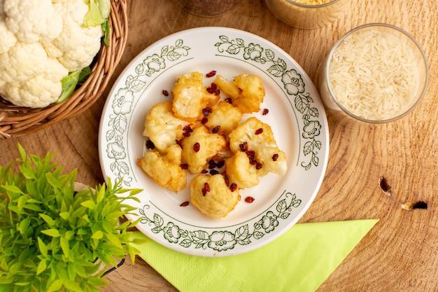 크림 나무 표면에 채소와 생 쌀과 함께 접시 안에 요리 슬라이스 콜리 플라워의 상위 뷰
