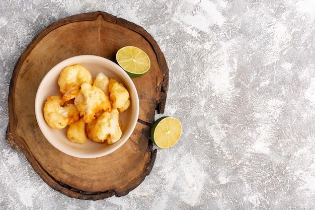Вид сверху приготовленной нарезанной цветной капусты внутри тарелки с лимоном на серо-светлой поверхности