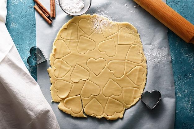 青い背景の上のハートの形をしたクッキー生地の上面図。料理のコンセプトのプロセス