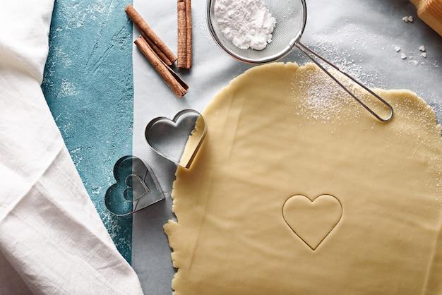 中央にハートのクッキー生地の上面図、粉砂糖、シナモンスティック、ストレーナー、青い背景の上の金属の形