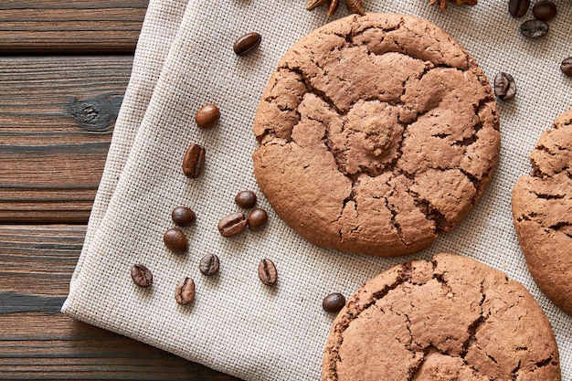 クッキーとコーヒー豆の茶色のナプキンと木製の背景の上から見る