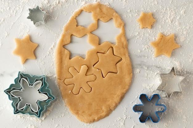 Вид сверху на тесто для печенья в форме снежинок