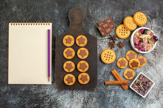 Вид сверху печенья на деревянном блюде с блокнотом и ручкой с мисками сухих цветов на серой земле