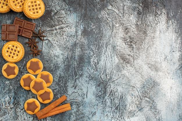 Вид сверху на печенье с палочками корицы и шоколадные конфеты на левой стороне серой земли