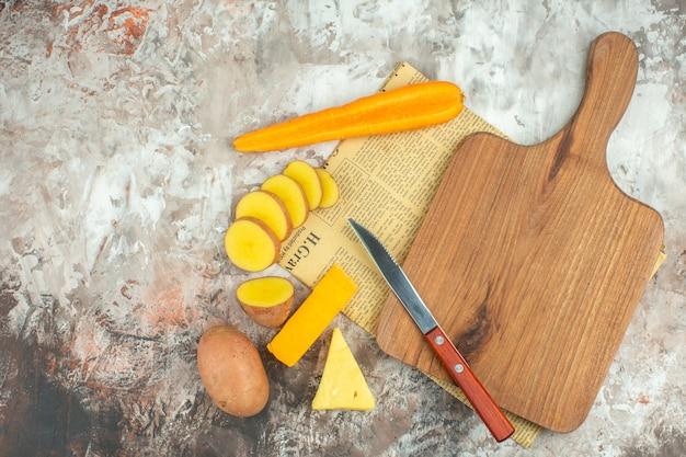 さまざまな野菜と2種類のチーズナイフと混合色の背景の古い新聞の木製まな板と料理の背景の上面図