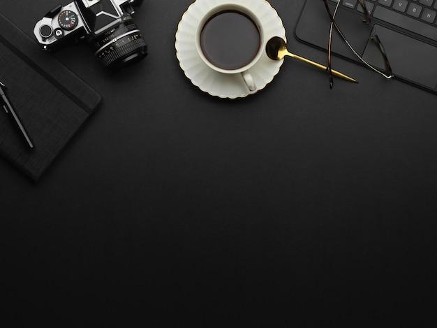 Вид сверху копировального пространства на черном столе с кофейной чашкой, камерой и принадлежностями в комнате домашнего офиса