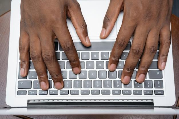 노트북 키보드에 입력 카피라이터 손의 상위 뷰. 집에서 프리랜서 프로젝트를 일하는 남자, 정보 검색