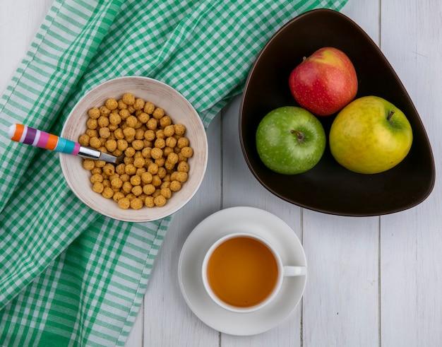白い表面に色のスプーンと色のリンゴと市松模様のタオルの上にコーンボールのトップビュー