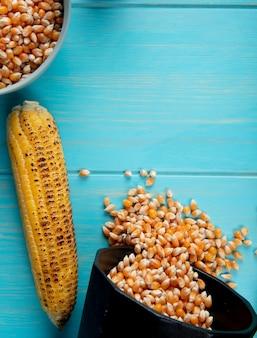 トウモロコシの穂軸とトウモロコシの種子が青い表面にポットからこぼれ出るのトップビュー