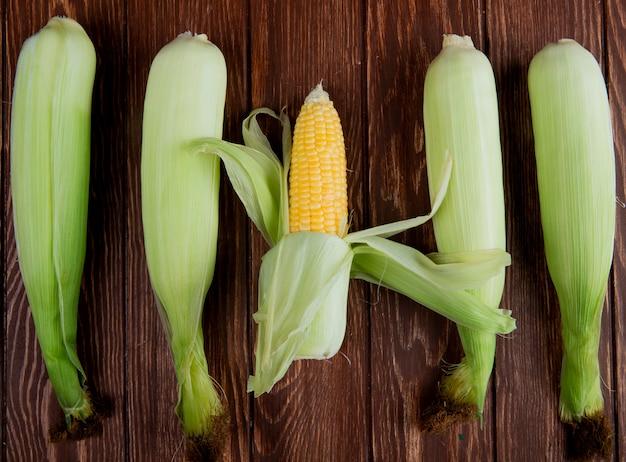 Вид сверху початков кукурузы с оболочкой на деревянной поверхности