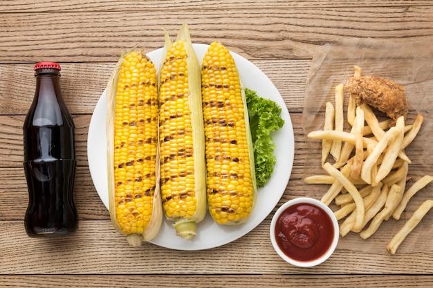 Вид сверху кукурузы на тарелку с картофелем фри