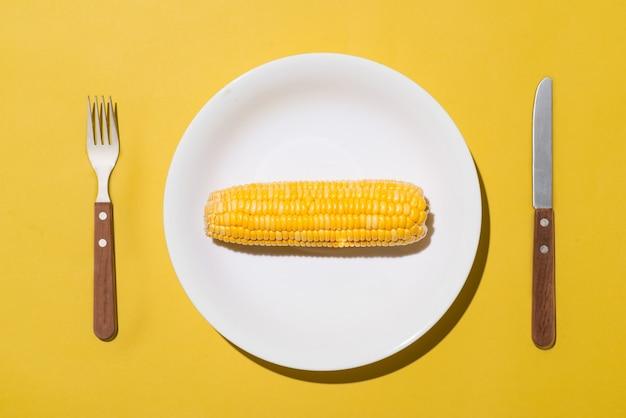 Вид сверху кукурузы на белой тарелке с ножом и вилкой на желтом фоне