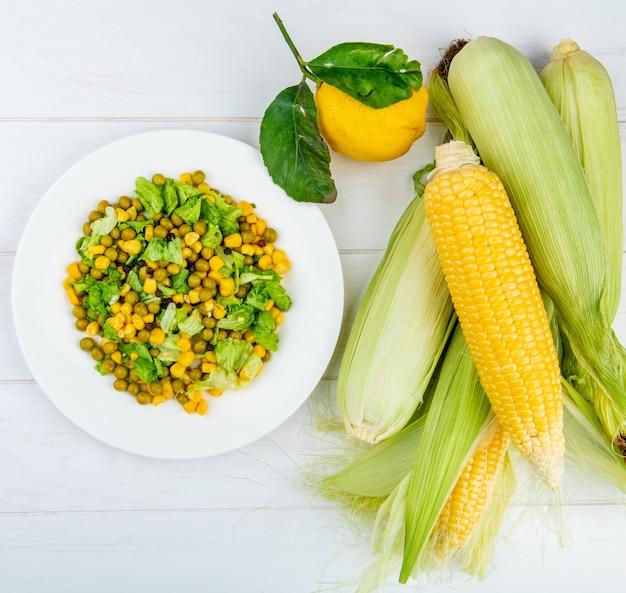 Вид сверху салат из кукурузы и початков кукурузы с лимоном на деревянной поверхности
