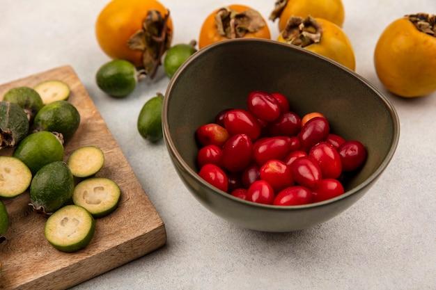 灰色の表面に柿が付いている木製のキッチンボード上で分離された全体と半分の新鮮なフェイジョアとボウルの上のコーネリアンチェリーの上面図