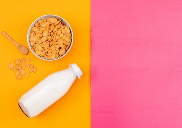 コーンフレークとピンクと黄色の背景の水平にコピースペースでミルクのトップビュー