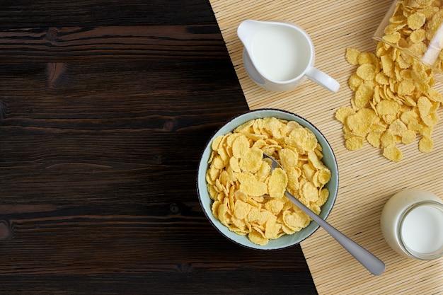 나무 배경에 우유와 함께 그릇에 콘플레이크의 상위 뷰 프리미엄 사진