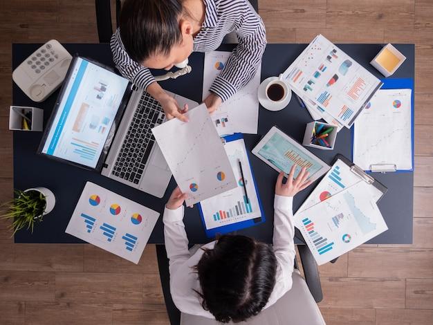 좋은 팀워크를 하고, 재무 전략을 세우고, 서류상의 차트를 보고, 책상에 앉아 있는 기업 비즈니스 사람들의 상위 뷰. 문서가 있는 태블릿 pc와 노트북을 사용하는 마케팅 팀.