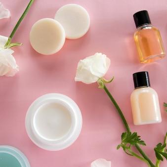 분홍색 배경에 있는 화장품과 섬세한 꽃의 꼭대기. 웰빙 뷰티 트리트먼트. 유기농 스킨케어 제품