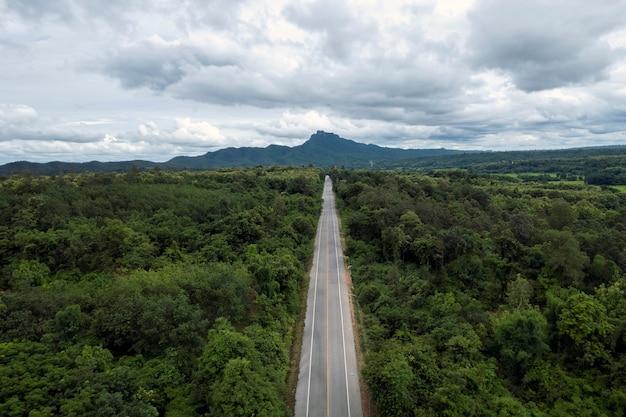 Вид сверху на сельскую дорогу, проходящую через зеленый лес и гору