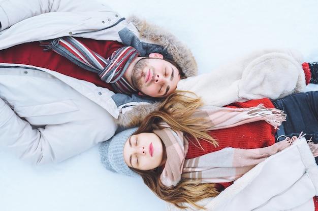 カップルの男性と女性の平面図は、冬の服を着て雪の上に横たわり、目を閉じて一緒に夢を見る