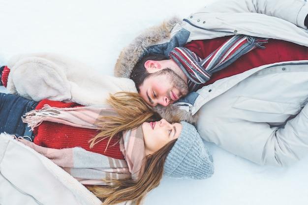 カップルの男性と女性の平面図は、冬の服を着て雪の上に横たわって、愛を込めてお互いを見ています