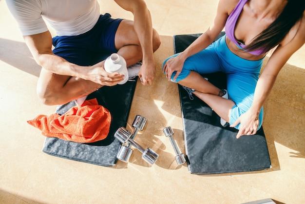 足を組んでマットの上に座って、トレーニングから休んでいるカップルの平面図です。水のボトルを保持している男。ジムのインテリア。