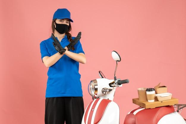 パステル ピーチ色の背景に停止ジェスチャーを作るコーヒー ケーキとオートバイの隣に立っている医療マスクの宅配便の女の子のトップ ビュー