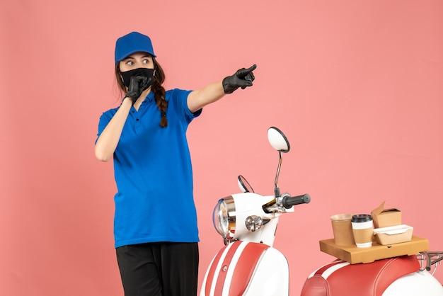 파스텔 복숭아 색 배경에 앞으로 가리키는 커피 케이크와 함께 오토바이 옆에 서있는 의료 마스크에 택배 소녀의 상위 뷰