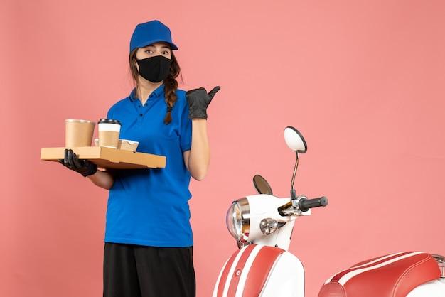 パステル ピーチ色の背景を指すコーヒーの小さなケーキを保持しているオートバイの隣に立っている医療マスク手袋を着た宅配便の女の子のトップ ビュー