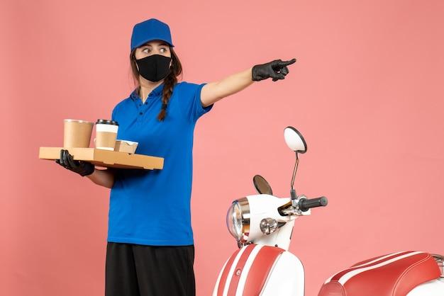 パステル ピーチ色の背景に前方を指すコーヒーの小さなケーキを保持しているオートバイの隣に立っている医療マスク手袋を着た宅配便の女の子のトップ ビュー