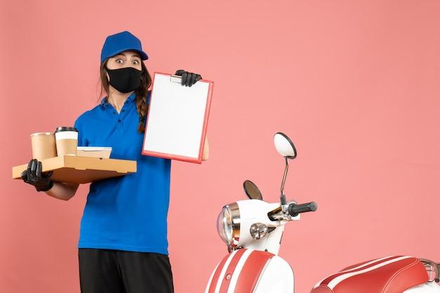파스텔 복숭아 색 배경에 문서와 커피 작은 케이크를 들고 오토바이 옆에 서있는 의료 마스크 장갑을 끼고 택배 소녀의 상위 뷰