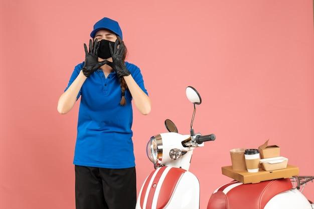 파스텔 복숭아 색 배경에 누군가를 호출 케이크에 커피와 함께 오토바이 옆에 서있는 의료 마스크 장갑을 착용하는 택배 소녀의 상위 뷰