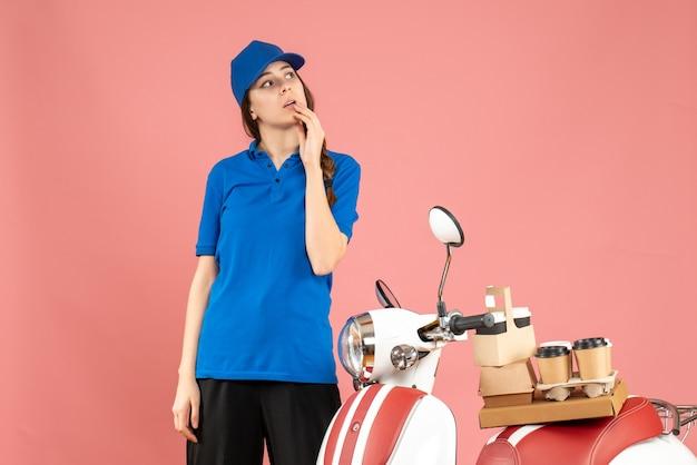 パステル ピーチ色の背景に深く考えてコーヒーと小さなケーキを乗せたバイクの隣に立つ宅配便の女性のトップビュー