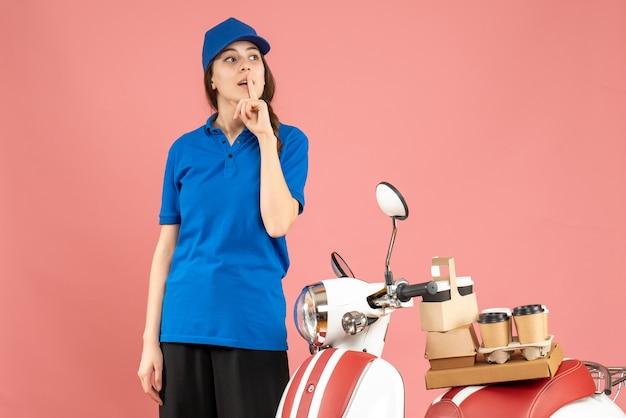 コーヒーと小さなケーキを乗せたバイクの隣に立ち、パステルピーチ色の背景に沈黙のジェスチャーをする宅配便の女性のトップビュー