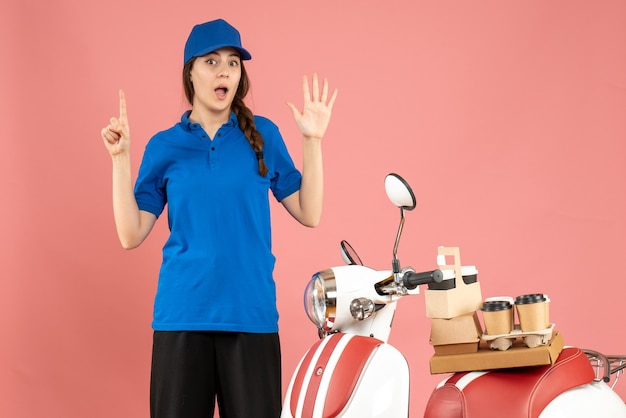 コーヒーと小さなケーキを乗せたバイクの隣に立つ宅配便の女性のトップビューで、パステルピーチの色の背景に5つ上向き