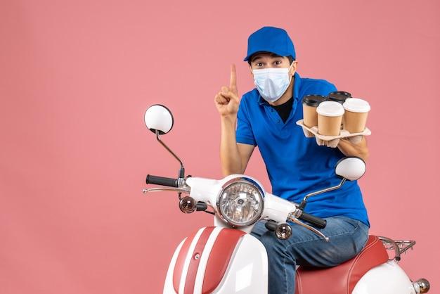 パステル調の桃の背景に満足した注文を示すスクーターに座っている帽子をかぶったマスクの宅配便のトップビュー