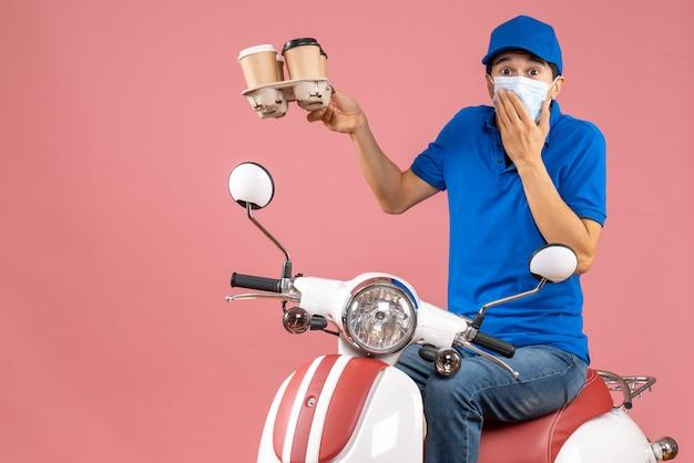 パステル調の桃の背景に驚きの注文を示すスクーターに座っている帽子をかぶったマスクを着た宅配便のトップビュー