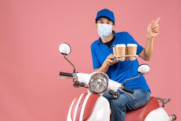 파스텔 복숭아 배경에 가리키는 주문을 보여주는 스쿠터에 앉아 모자를 쓰고 마스크에 택배 남자의 상위 뷰