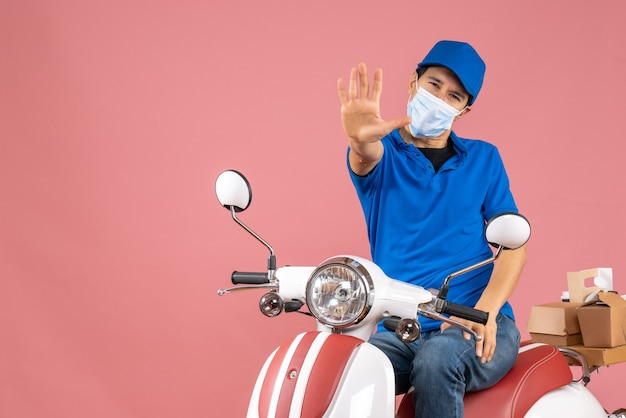 スクーターに座って、パステル カラーの桃の背景に 5 つを示す帽子をかぶった医療マスクの宅配便の男のトップ ビュー