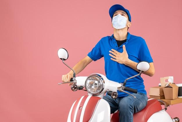 パステル調の桃の背景に誇りを持ってスクーターに座っている帽子をかぶった医療マスクの宅配便の男性のトップビュー