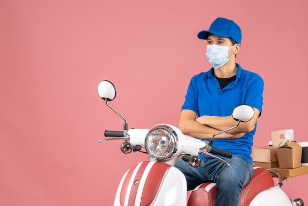 パステル調の桃の背景に何かを注意深く見ているスクーターに座っている帽子をかぶった医療マスクの宅配便の男性のトップビュー